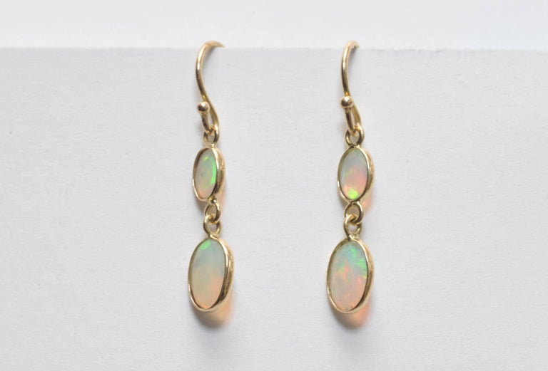 Double drops of faceted opals set in 18K gold.  I love the way these are set--the pointed faceted part of the stone is the part that faces out.--creating dimension and light.  On 18k gold French wires, for pierce ears.  Carat weight of opals is