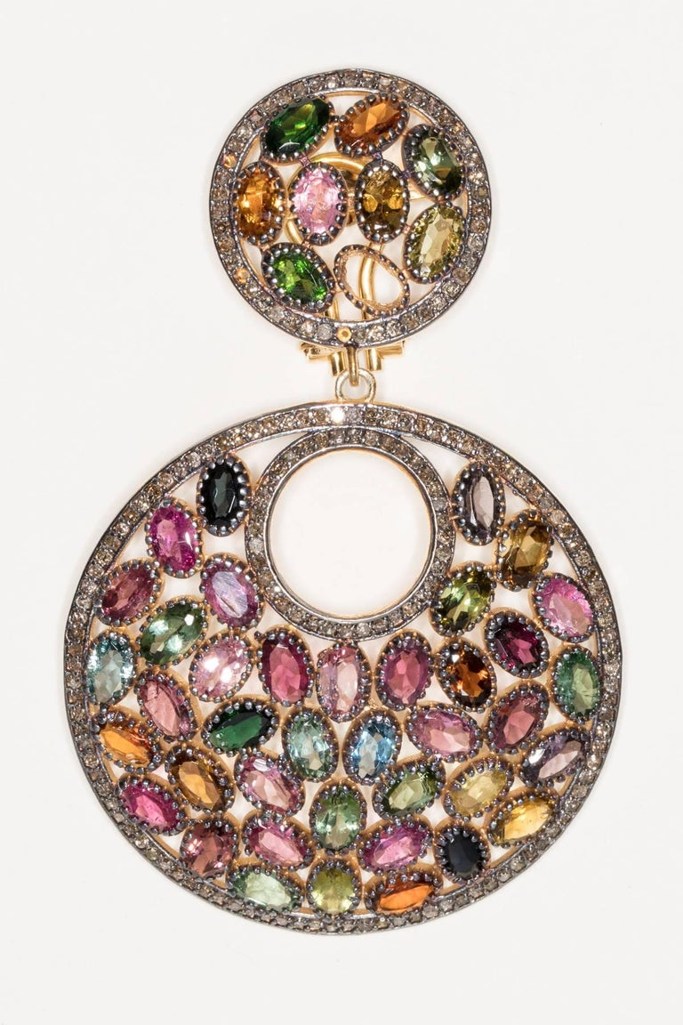 A mosaic of faceted oval tourmalines bordered with pave`set diamonds set in sterling silver with 18K gold post.  All natural stones of great quality in a complete color spectrum of tourmalines.  Diamond weight is 1.95 carats, tourmalines are 24.10
