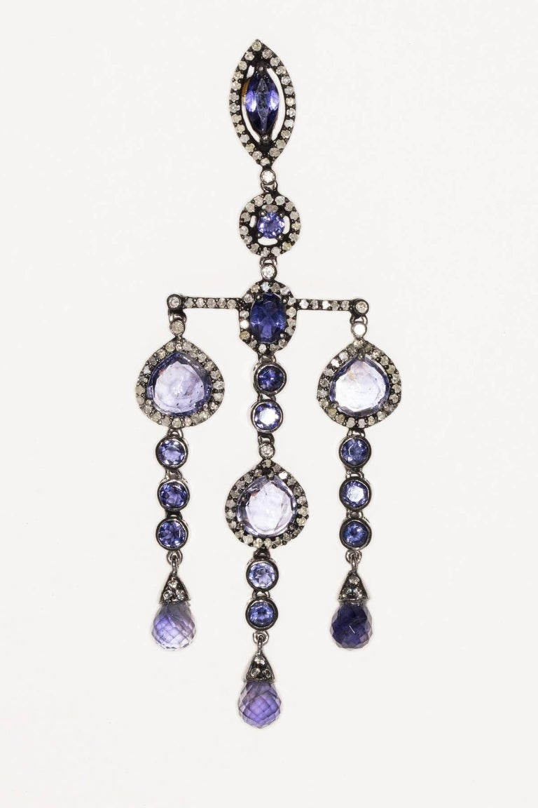 In an Art Deco design style, faceted iolite of various cuts bordered in pave`-set diamonds set in black oxidized sterling silver with 18K gold post for pierced ears.  Unusual with great movement.  Carat weight of diamonds is 2.10; iolites are 17