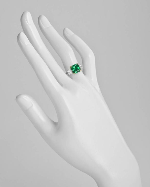 Colombian emerald and diamond ring, centering a fine octagonal-shaped step-cut emerald weighing 2.42 carats, flanked by a pair of colorless asscher-cut diamond shoulders weighing 1.05 total carats (D-E color/VS1-VS2 clarity), mounted in platinum
