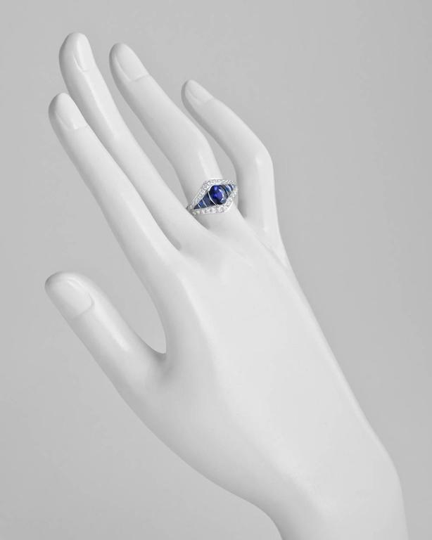 Sapphire and diamond three-row dress ring, showcasing a larger oval-shaped sapphire at center flanked by smaller calibre-cut sapphires, within a near-colorless round brilliant-cut diamond surround, mounted in platinum. Oval-shaped sapphire weighing
