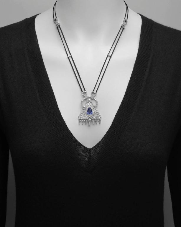 Sapphire and diamond pendant necklace, centering a triangular-shaped step-cut natural sapphire weighing 5.53 carats, surrounded by circular-cut diamonds in a triangular motif, with tapered baguette-cut and circular-cut diamond hanging fringe at