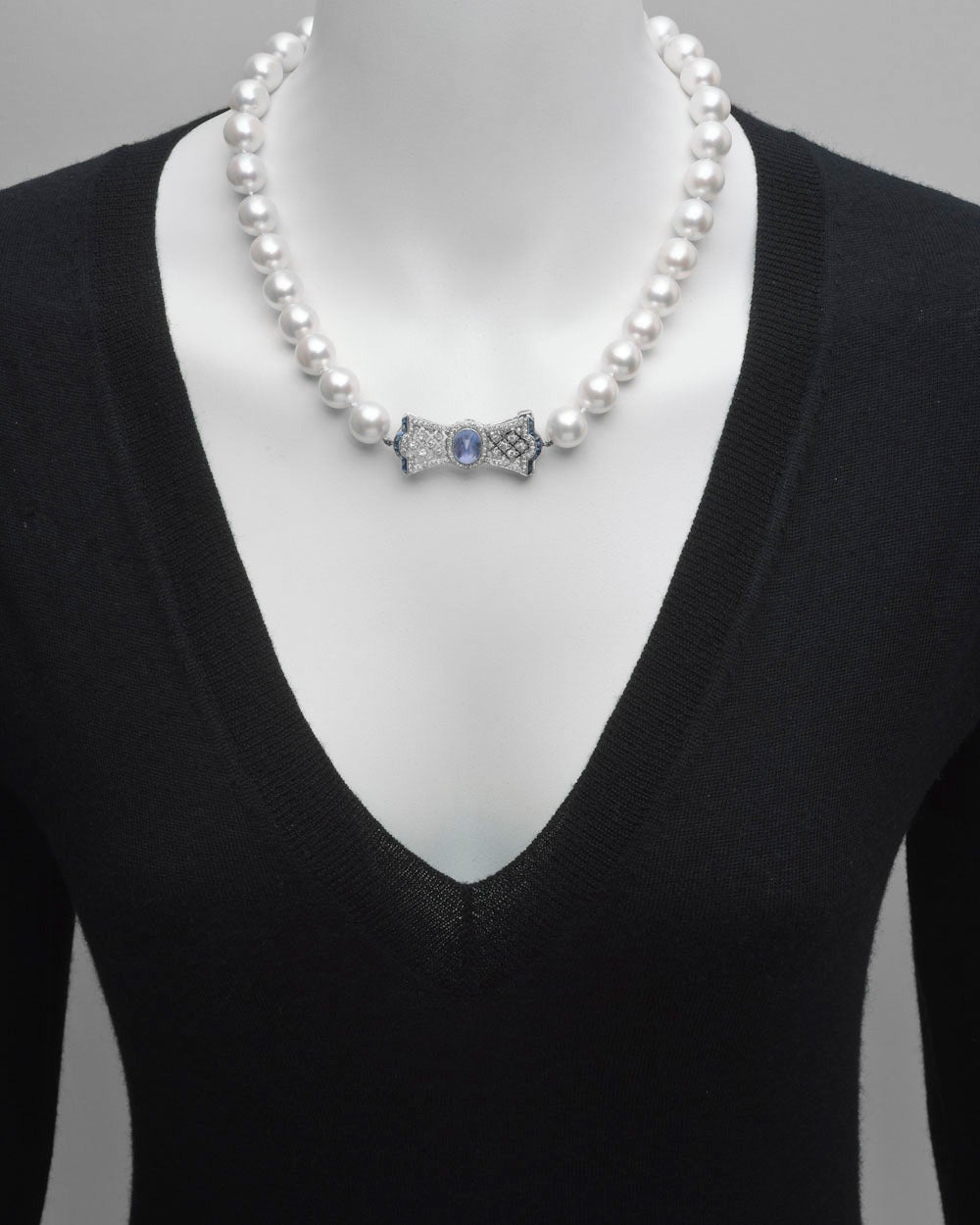 South Sea pearl necklace, showcasing fine cultured South Sea pearls with diameters ranging from 12.5mm to 12mm, strung on a hand-knotted silk cord, with a sapphire and diamond bow-shaped clasp in platinum, the clasp centering a cabochon-cut sapphire