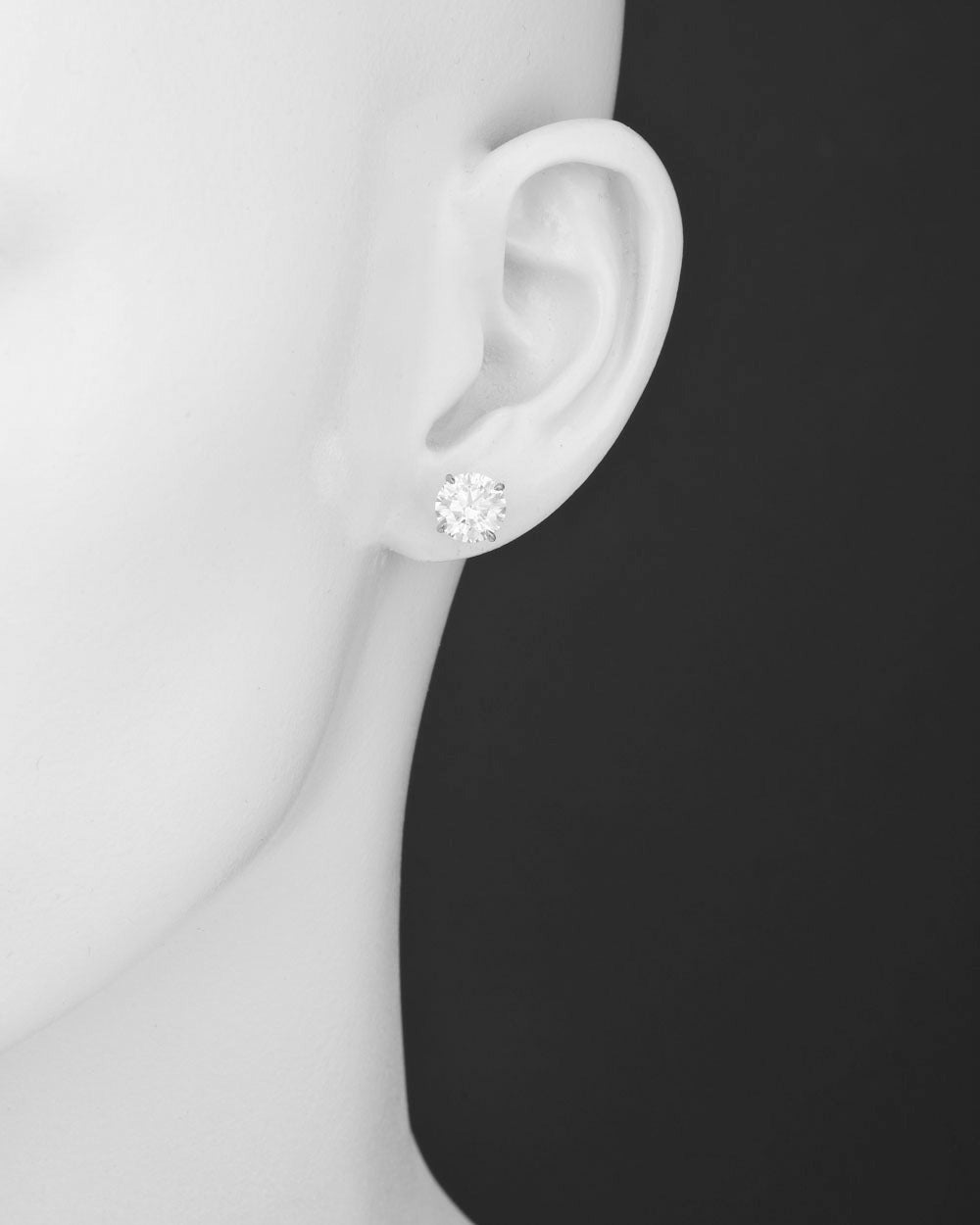 Round brilliant cut diamond stud earrings, showcasing a pair of near-colorless diamonds weighing 4.29 total carats, the diamonds secured in classic four prong platinum settings with posts and friction backs for pierced ears. The earrings are