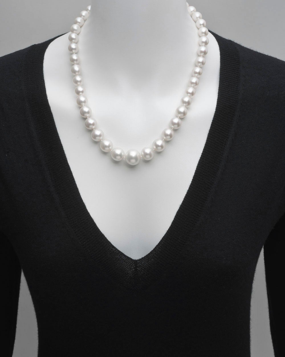South Sea pearl necklace, composed of cultured South Sea pearls with diameters ranging from 15mm to 10mm, strung on a hand-knotted silk cord, with a marquise-shaped diamond set clasp in platinum, the marquise-shaped diamond weighing approximately