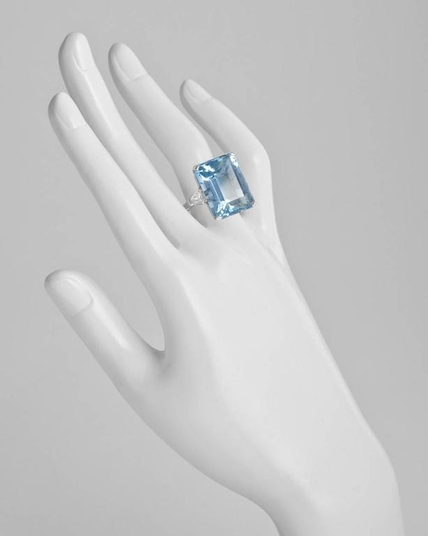 Aquamarine cocktail ring, centering a finely-colored step-cut aquamarine weighing 24.07 carats and measuring approximately 20 x 16mm, flanked by a pair of colorless shield-cut diamond shoulders weighing 1.52 total carats (both F-color), mounted in