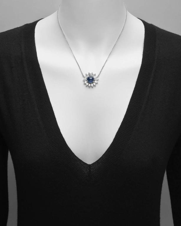 Sapphire and diamond cluster pendant necklace, showcasing an oval-shaped cabochon sapphire weighing approximately 7 carats, surrounded by near-colorless marquise-shaped diamonds weighing approximately 3.50 total carats (I-J color/SI clarity),