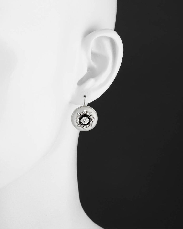 Drop earrings, showcasing a circular-shaped polished rock crystal centering an inset larger round-cut diamond within a carved black onyx frame and openwork round-cut diamond-set lattice, the earrings mounted in 18k white gold with a round-cut