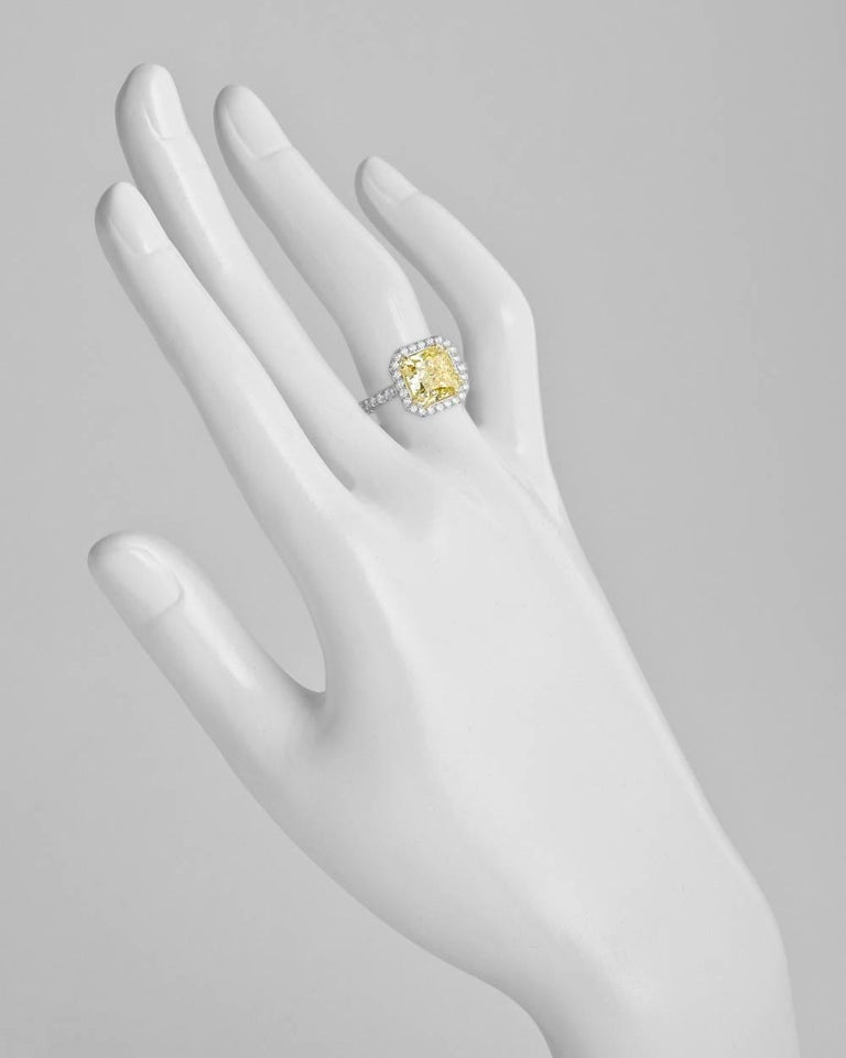 Yellow diamond engagement ring, centering a fine radiant-cut fancy yellow diamond weighing 4.01 carats with VS2-clarity, framed by round-cut white diamonds with partway round-cut white diamond-accented band, mounted in platinum and 18k yellow gold.