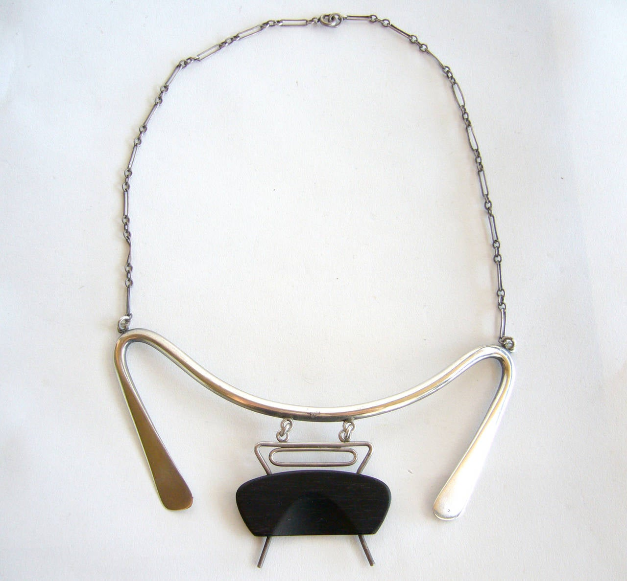 A rare, American abstract modernist sterling silver and exotic wood necklace, circa 1950's and designed by Irvin and Bonnie Burkee of Arizona.  Necklace is comprised of hand forged, curvilinear shaped sterling silver and a hinged, hand carved wood