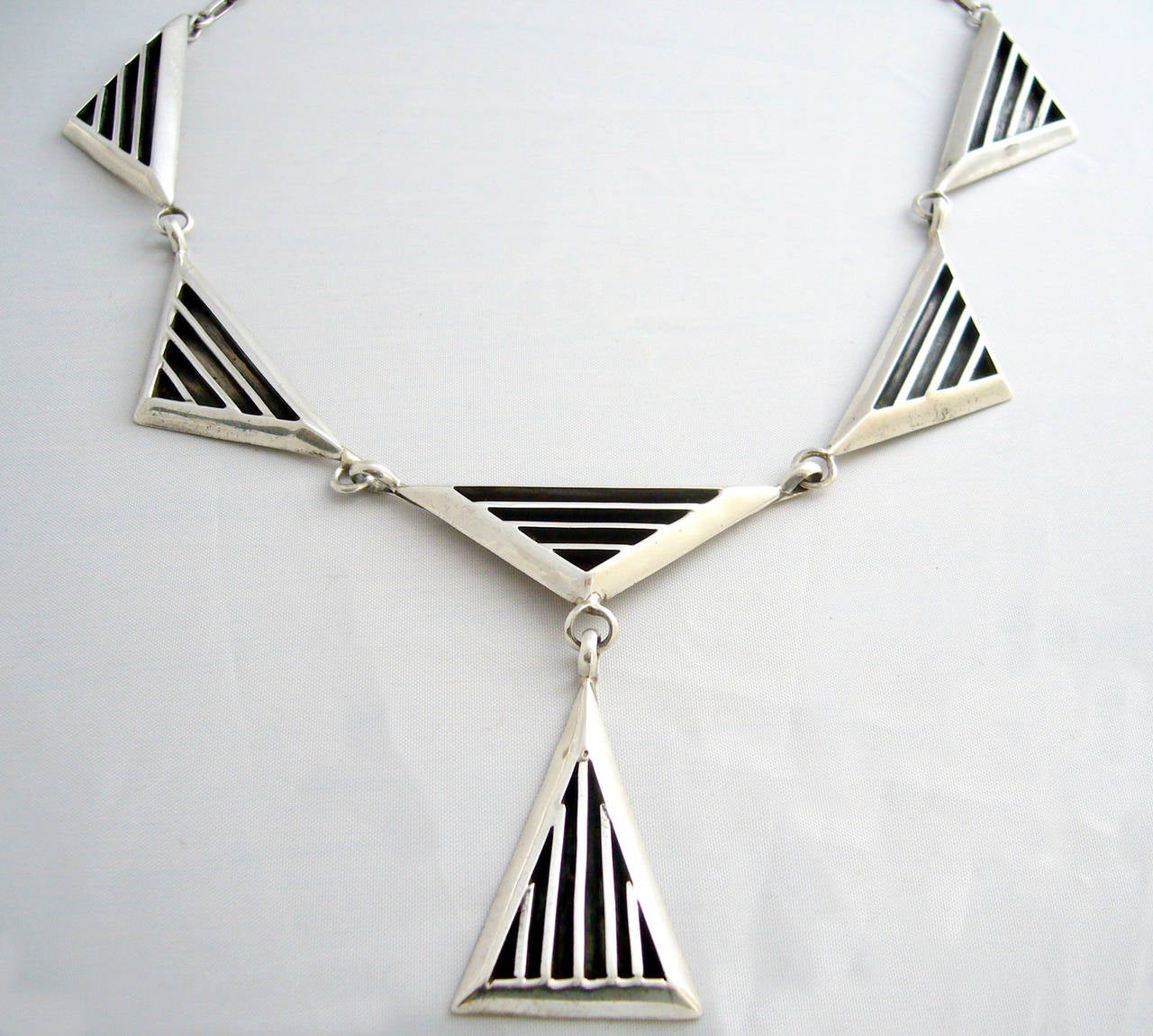 A sterling silver necklace with oxidized recessed design within triangle links by Jack Nutting of San Francisco circa 1960. Necklace has 18