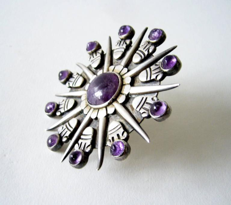 "Iconic Aztec sunburst amethyst and sterling silver brooch designed and created by William Spratling of Taxco, Mexico. Brooch measures a large 3"" in diameter and features 11 cabochon amethyst stones.  Signed on reverse with the ""WS"" hallmark,"