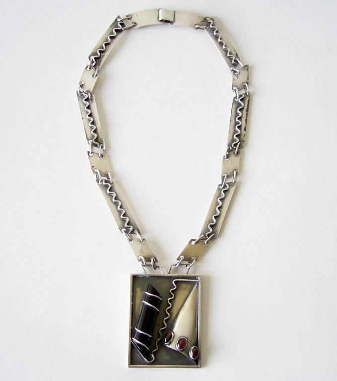 Sterling silver, onyx, amber or garnet surrealist necklace created by Idella La Vista of New York City, New York.  Necklace features a large piece of onyx threaded on to a sterling plaque along with other pieces of hand forged silver, created with