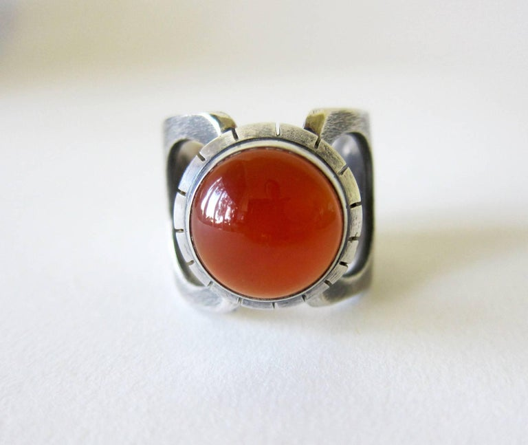 Handmade sterling silver modernist ring with carnelian cabochon created by James Parker of San Diego, California.  Ring is a finger size 11 to 11.5 and is signed with the artists' cypher of a conjoined JP.  Tests positive for silver and suitable for