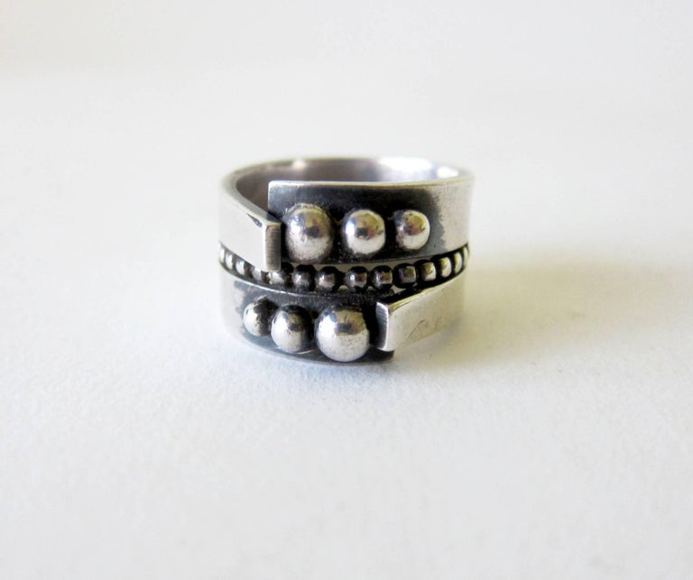 A very involved sterling silver ring with ball decoration on face and around the shank creat by James Parker of San Diego, California.  Ring is a finger size 8, shank measures 1/2