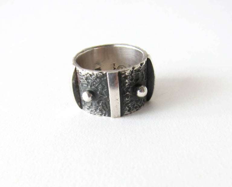 Sterling silver wide band ring featuring a studded design created by James Parker of San Diego.  Parker was an early member of the San Diego Allied Craftsmen Association which started in the 1940's.  His jewelry was featured in the show