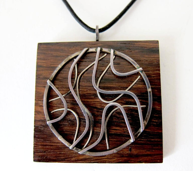California studio exotic wood pendant necklace with applied hand forged sterling design created by Milton Cavagnaro of Mill Valley, California.  Pendant measures 2
