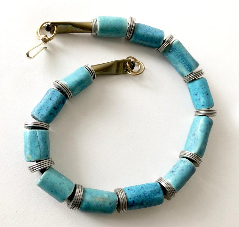 Handmade necklace of twelve cylindrical mottled turquoise beads separated by steel washers, created by Doyle Lane of Los Angeles, California.  Necklace measures 20