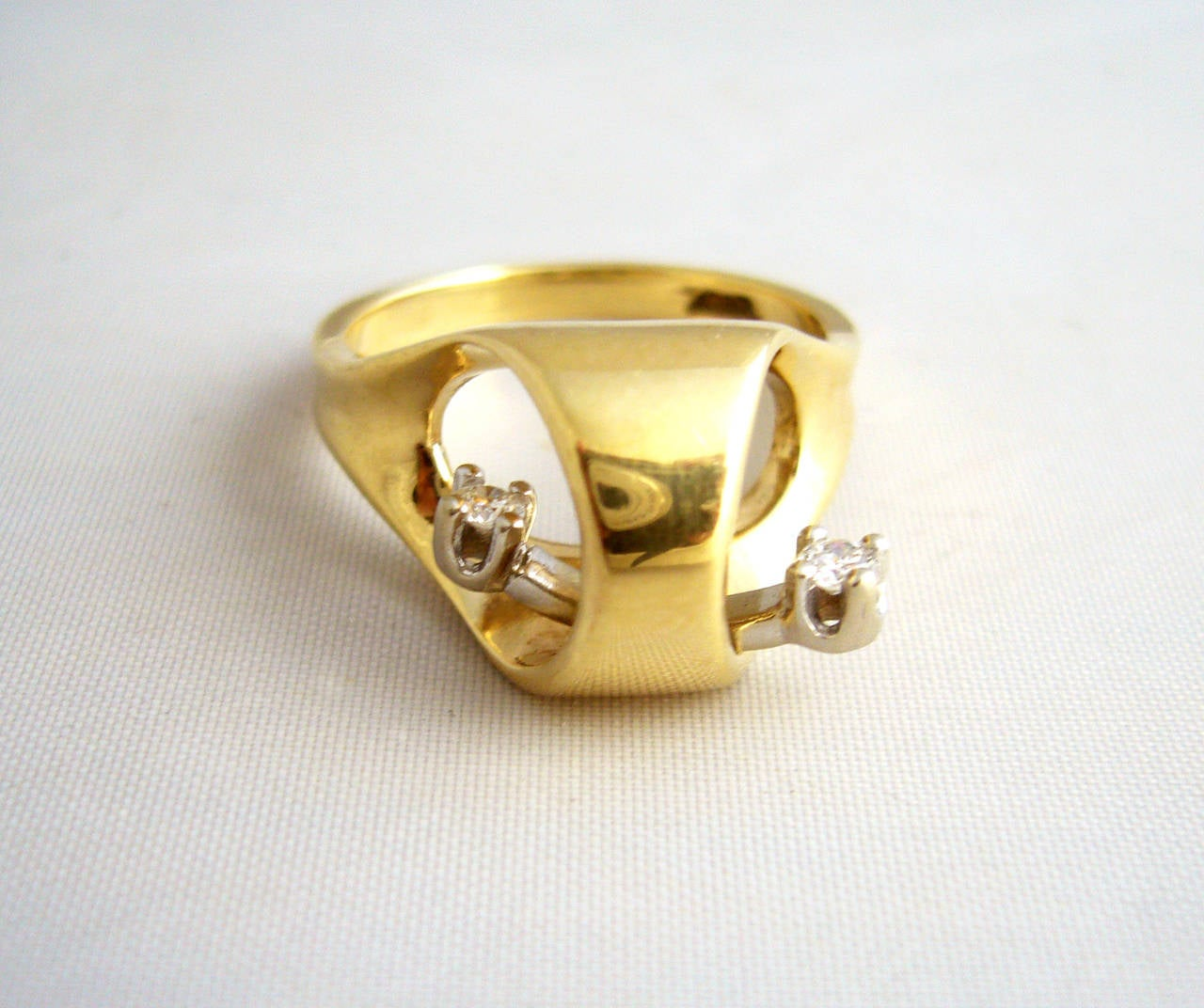 An interesting 14k gold and diamond ring circa 1960's.  Diamonds are suspended within the ring, set in white gold have a swinging, teeter totter movement.  Cool alternative to an engagement or wedding ring.  A finger size 6.5 and signed 14k.  In