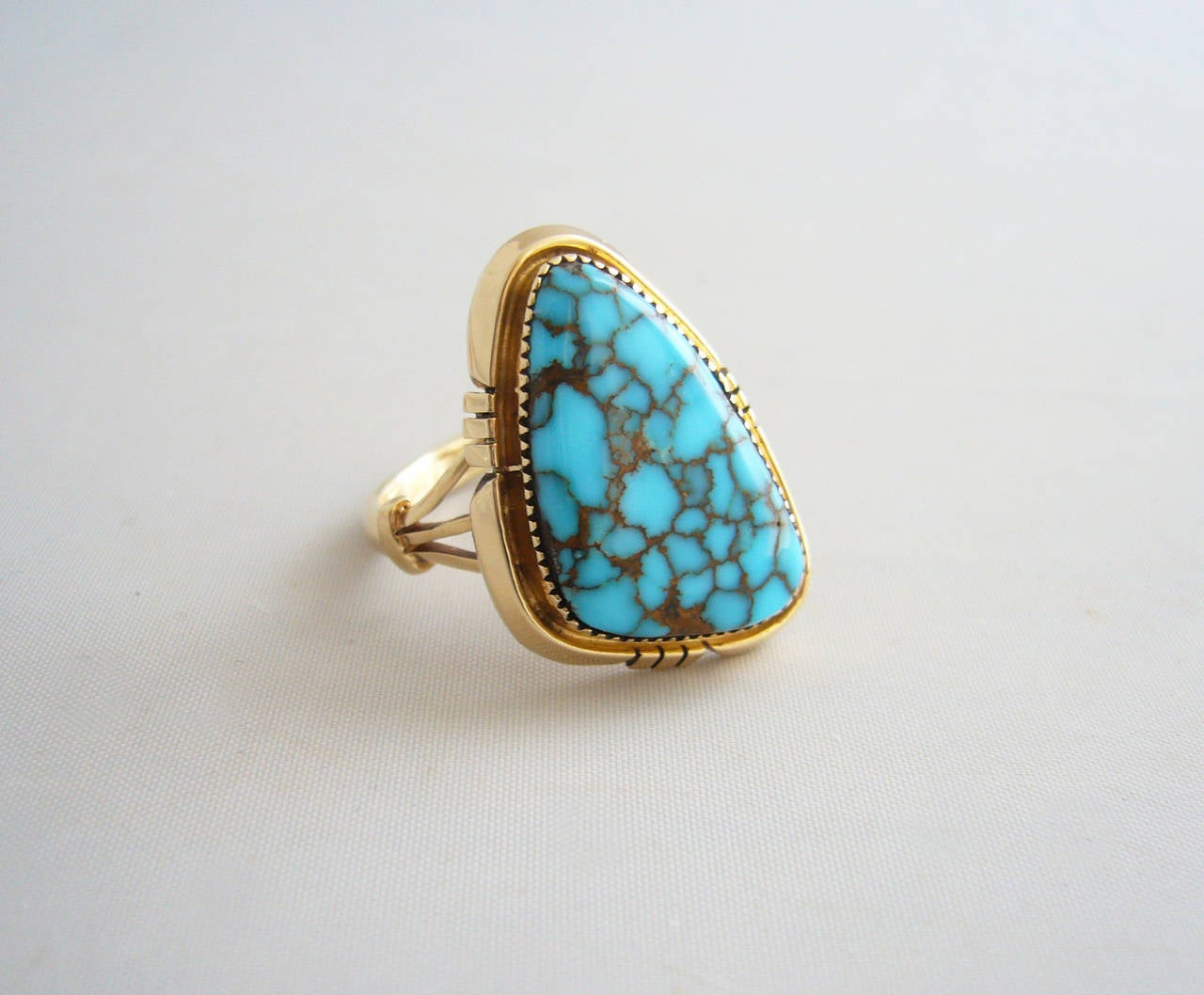 An exceptional 14K gold ring with triangular Blue Mountain or Kingman turquoise stone set within.  Face of the ring measures 1 1/8