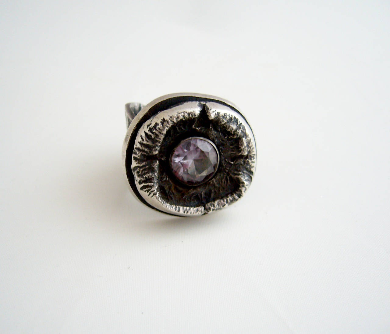 A sterling silver and a  amethyst ring created by James Parker of San Diego, California circa 1960's.  Faceted amethyst is nestled within a brutalist cave-like setting.  Ring is a finger size 9 to 9.5.   A great, unconventional alternate to a modern