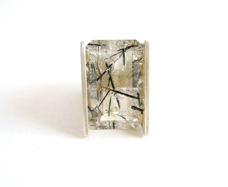 An exceptional faceted rutilated quartz ring created by Heidi Abrahamson of Phoenix, Arizona.  Ring features a beautiful example of an emerald cut rutilated quartz stone which has been tension set and suspends high above the finger.  Ring is