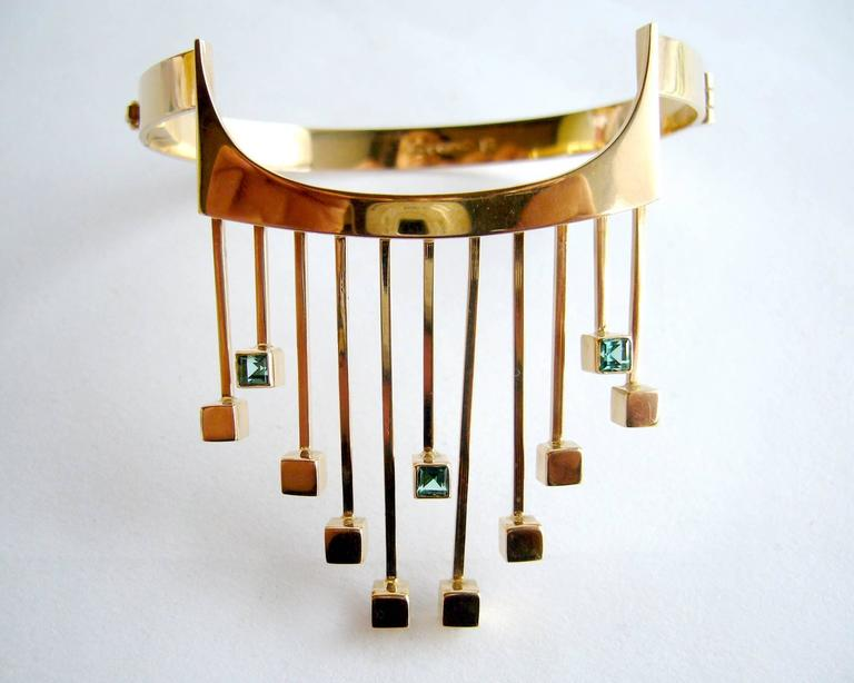 A rare, Finnish modernist 14k gold and tourmaline bracelet designed by Paula Häiväoja and executed by master goldsmith, Timo Nupponen.  Bracelet features golden fringe accented with square-cut greenish-blue tourmalines at the ends and a wearable