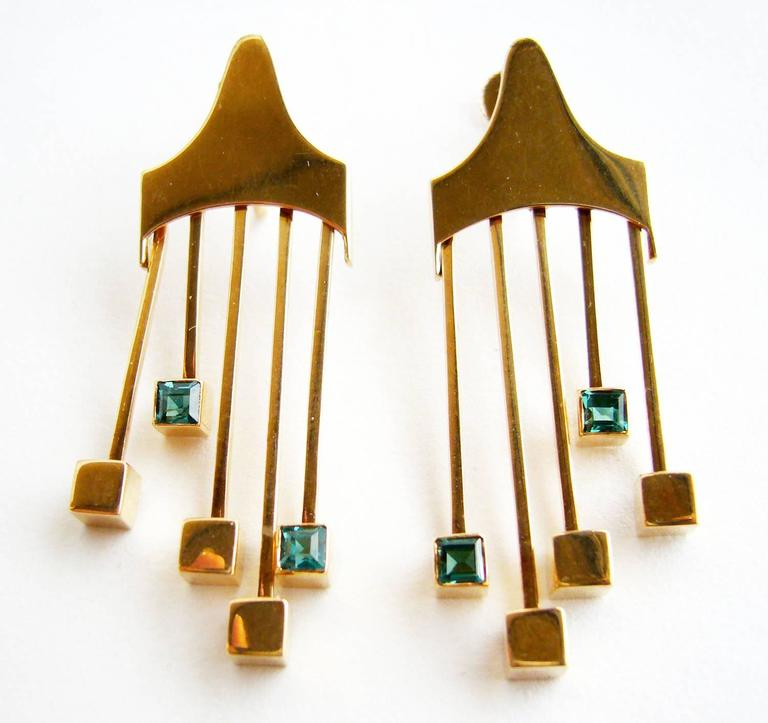 Rare, Finnish modernist 14k gold and tourmaline screw back earrings designed by Paula Häiväoja and executed by master goldsmith, Timo Nupponen for Kaunis Koru.  Earrings feature kinetic gold fringe with blueish green square tourmaline on the tips