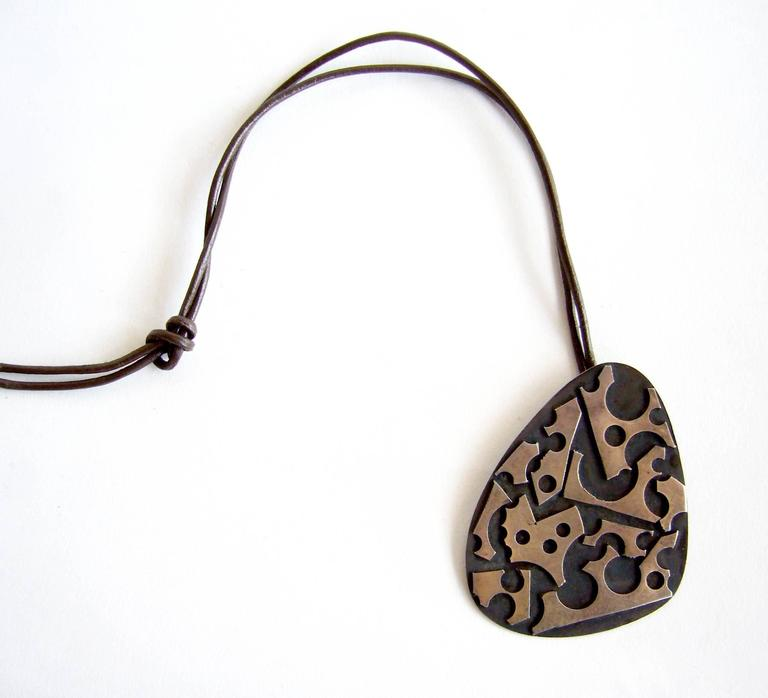 Oxidized sterling silver pendant created by silversmith James Parker of San Diego, California.  Parker was an early member of the Allied Craftsmen of San Diego which started in the 1940's.  His jewelry was featured in the show