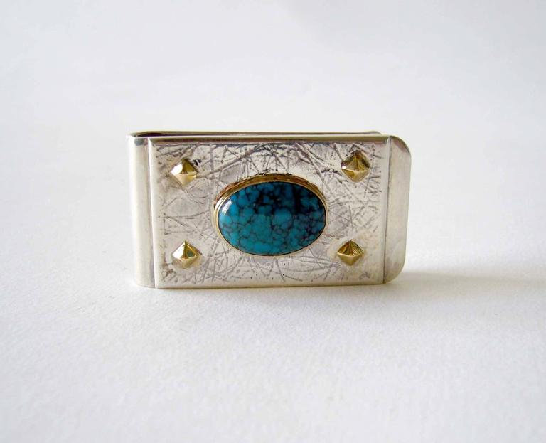 """Solid sterling silver money clip with oval spider web turquoise, of Southwest origin.  Spider web turquoise cabochon is set in 14K gold bezel along with four gold stud accents.  Money clip measures 1"""" by 1.75"""" and is signed DM within a"""