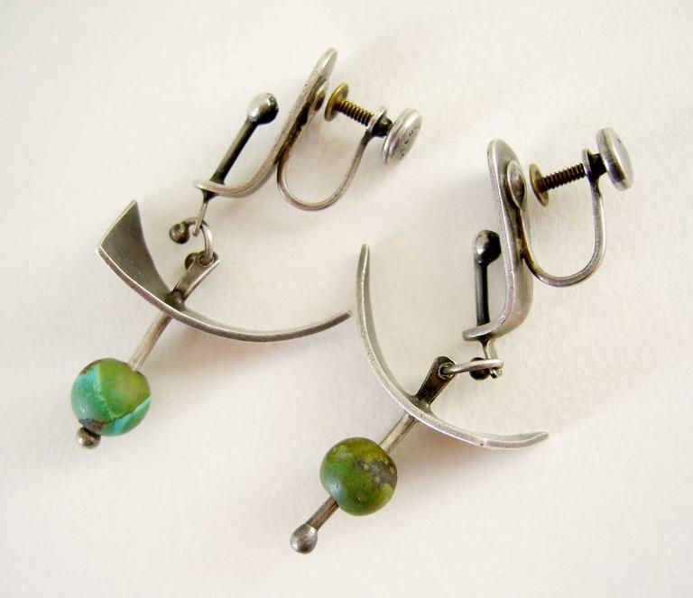 Abstract modern screwback earrings in sterling silver with turquoise bead accent circa 1950's.  Earrings were created by Ed Wiener of New York City, New York and measure 1.75