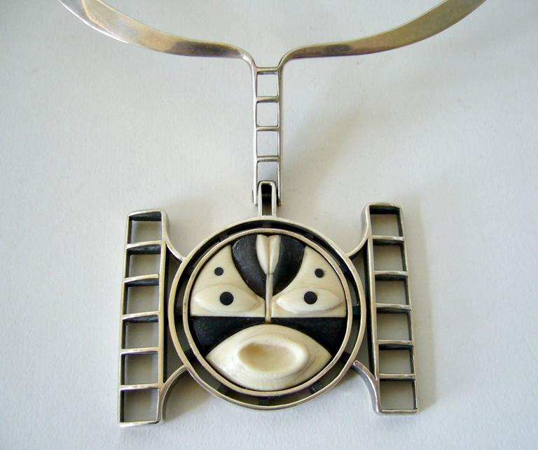 Modernist wood and sterling silver mask necklace created and signed by M. Sutton, circa 1950's.  Necklace has a wearable neck measurement of 16