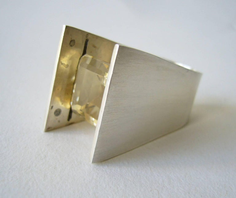 A faceted yellow quartz ring created by Heidi Abrahamson of Phoenix, Arizona.  Minimalist ring features a beautiful example of a square cut yellow quartz stone which has been tension set and suspends high above the finger.  Ring is approximately a