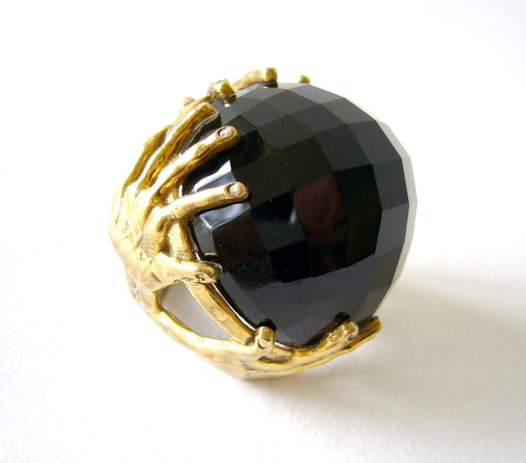 Large faceted smokey quartz sphere upheld by a surrealist bronze hands setting.  Sphere stands about .75