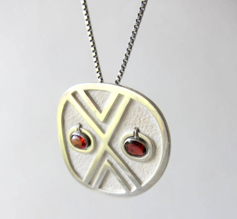 Silver pendant necklace with kinetic, hanging garnet eyes created by Oswaldo Guayasamin of Ecuador.  Pendant measures 1.5