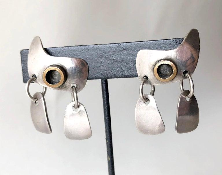 Sterling silver and brass kinetic earrings created by New York surrealist jeweler, Sam Kramer.  Earrings measure 1.5