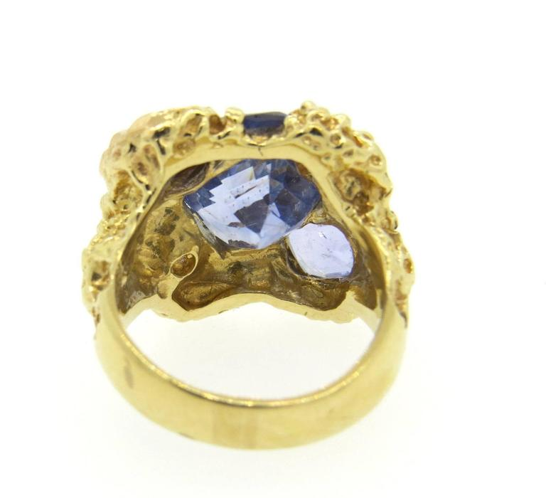 A 14k yellow gold ring set with six natural sapphires totaling approximately 11 carats and a H/SI2 diamond weighing 0.11ct.  The ring is a size 5 3/4, and the ring top is 20mm x 23mm.  The weight of the ring is 13.8 grams.  Comes with EGL