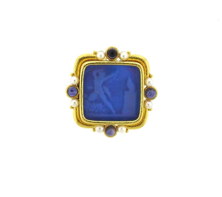 An 18k yellow gold brooch, designed by Elizabeth Locke, featuring Venetian glass intaglio, backed with mother of pearl, surrounded with pearls and blue sapphire cabochons. Brooch has a hidden bale to be worn as a pendant, measures 42mm x 42mm.