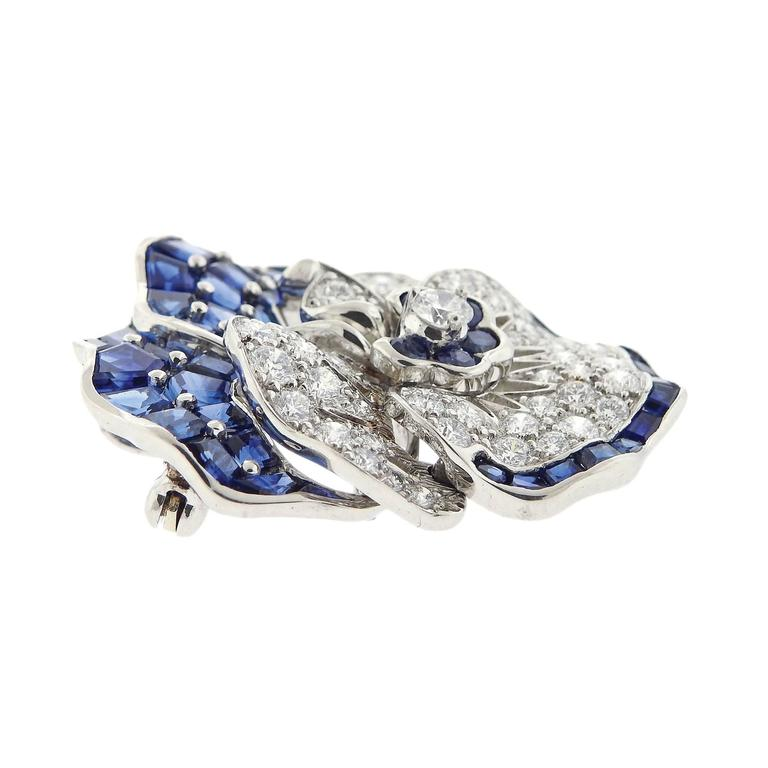 Iconic platinum pansy flower brooch, crafted by Oscar Heyman, decorated with approximately 3.25ctw in diamonds and 9.00ctw in blue sapphires. Brooch measures 35mm x 33mm. Marked: pt900, 10% irid, Maker's mark, 200174. Weigh of the piece - 23.8 grams.