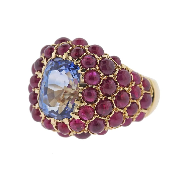 Impressive 18k yellow gold ring, crafted by Verdura, featuring an approximately 6.80ct blue sapphire in the center, surrounded with ruby cabochons.  Ring is a size - 7, ring top is 20mm wide. Marked: Verdura, 18k. Weight - 15.9 grams