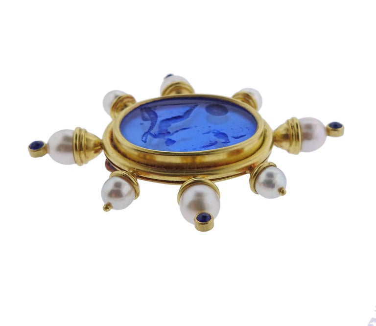 An 18k yellow gold large brooch, crafted by Elizabeth Locke, set with iconic Venetian Glass intaglio in the center, surrounded with pearls and sapphires. Brooch measures 65mm x 73mm. Marked with 18k and Locke hallmark. Weight of the piece - 36.2