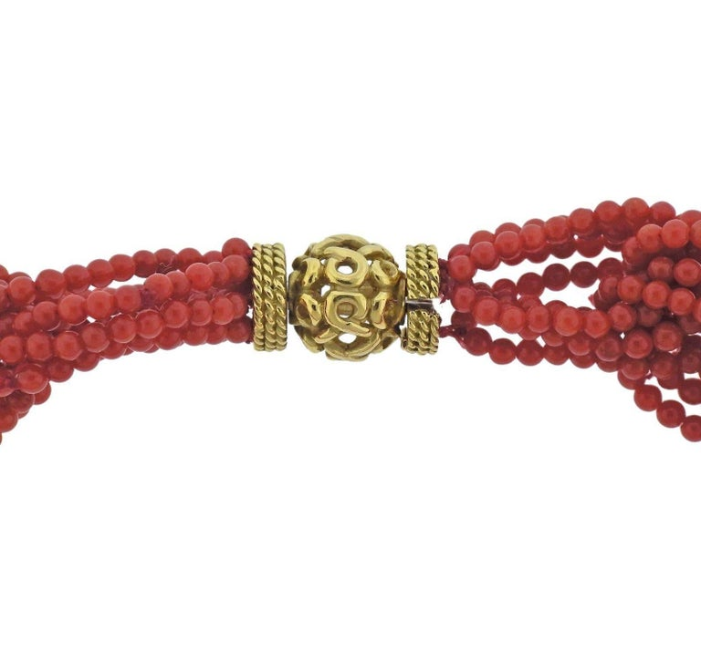 An 18k yellow gold necklace set with 2.5mm coral beads.  The necklace is 16 1/4