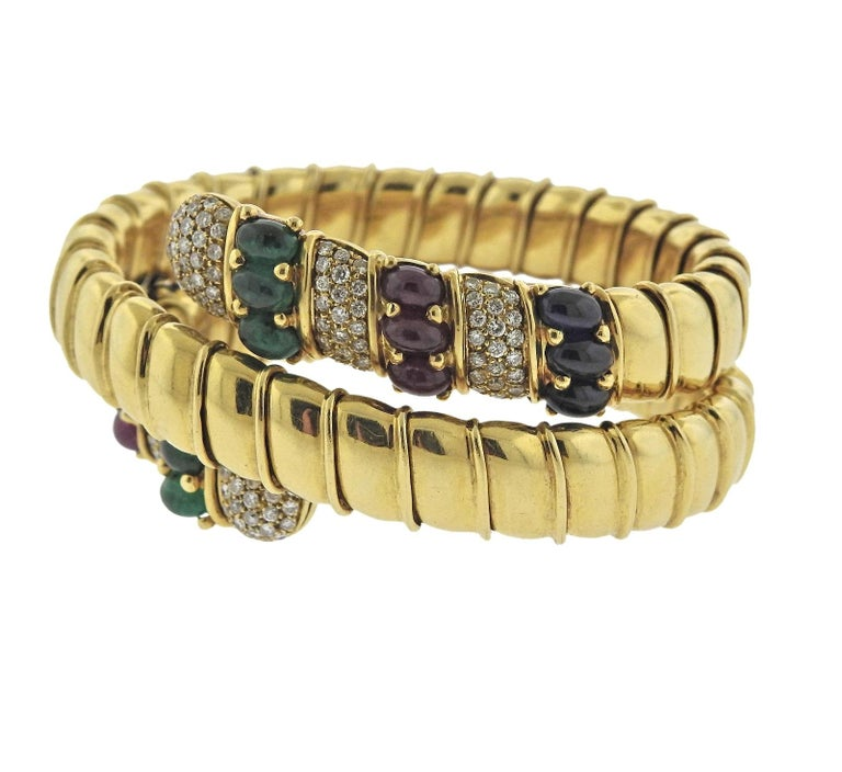 Beautiful 18k gold Italian crafted wrap bracelet, featuring sapphire, emerald and ruby cabochons, surrounded with approximately 2.40ctw in VS/GH diamonds. Bracelet will fit approx. 7