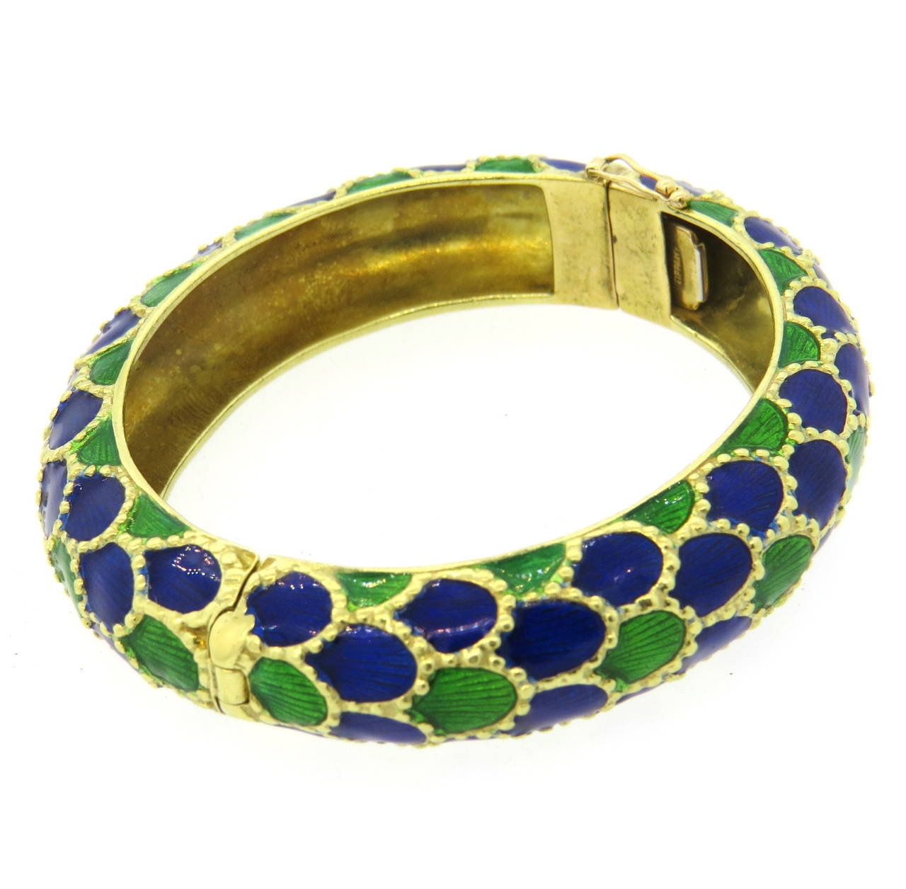 An 18k yellow gold bangle with a scale motif, coated with blue and green enamel.   the bangle comfortably fits up to a 7