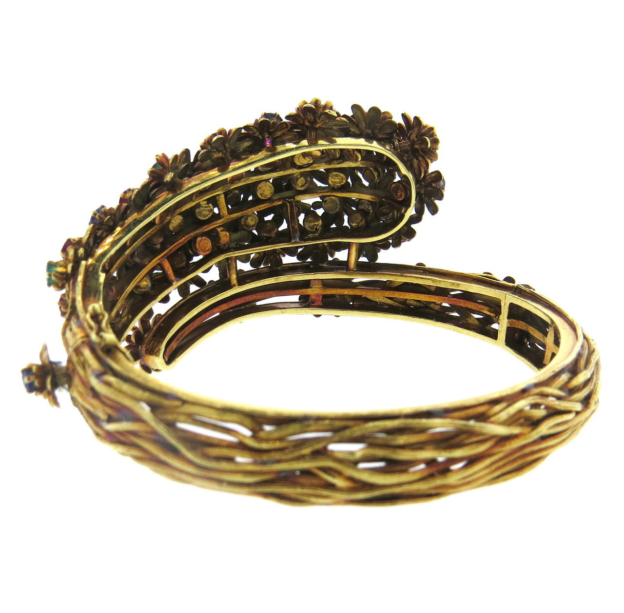 Zolotas Greece 18k gold bangle, featuring flowers, each set with diamond,sapphire,ruby or emerald in the center. Bracelet will comfortably fit  up to 7