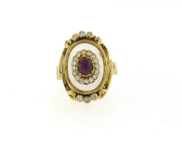 An 18k yellow gold ring, crafted by Ilias Lalaounis, featuring frosted crystal top, 5.7mm x 4.8mm ruby cabochon in the center, surrounded by approx. 0.40ctw in diamonds. Ring size 6 3/4, ring top is 25mm x 20mm. Marked: A21, 750, Greece, makers