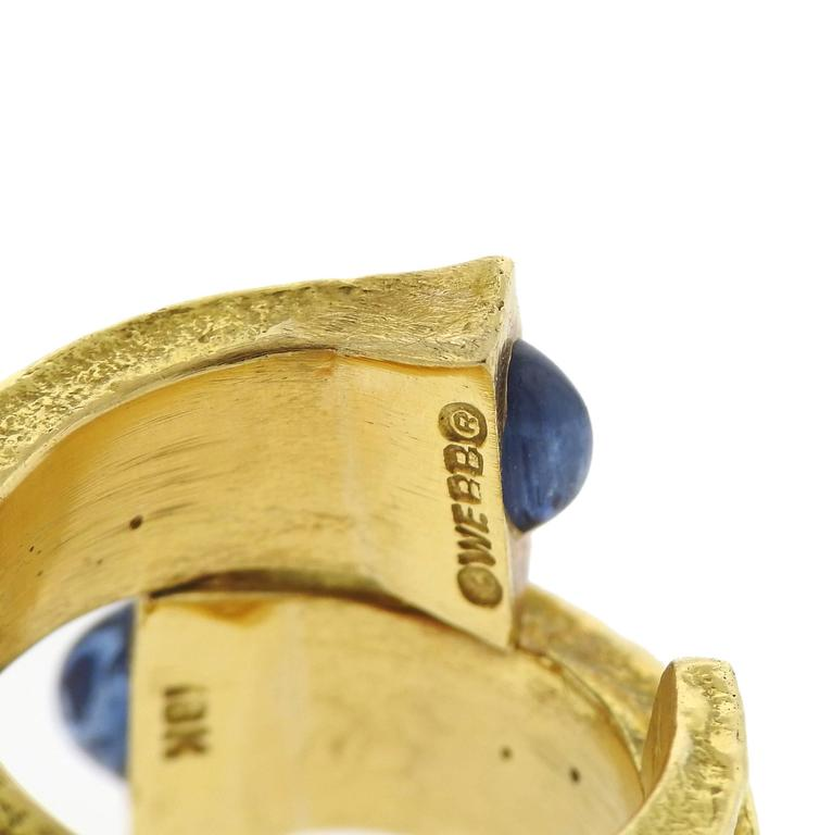 An 18k yellow gold ring, featuring wrap around nail design, adorned with blue sapphire cabochons. Crafted by David Webb, Ring size - 6 1/4, ring top is 20mm at widest point. Marked: Webb, 18k. Weight of the ring - 26.1 grams