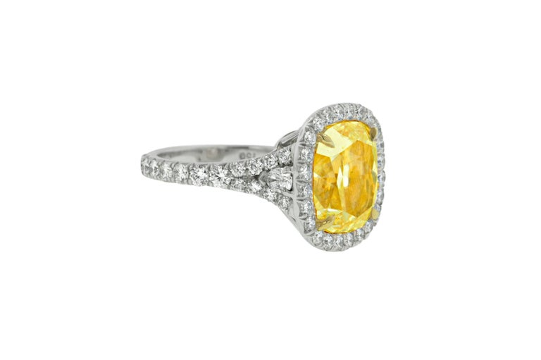 Platinum and 18 Karat Yellow Gold Fancy Yellow Diamond Ring, The center stone is 7.65 Carats Fancy Yellow in Color, VS2 in Clarity cushion cut diamonds, surrounded by 1.60 Carats of white diamonds around.