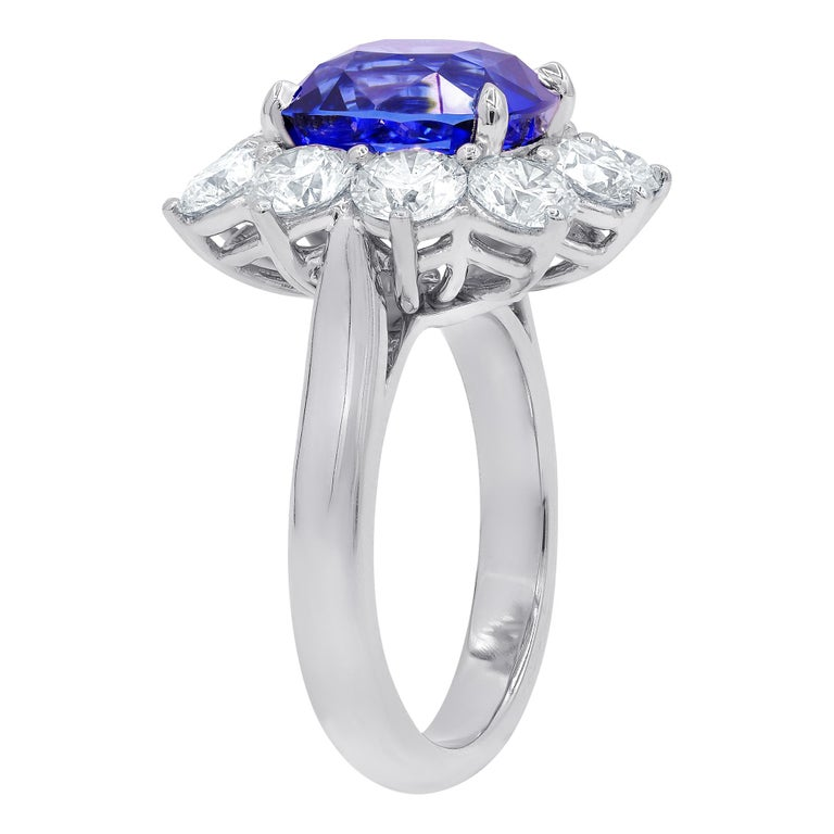 Platinum Cushion cut Sapphire and Diamond Ring, the center stone is cushion cut Royal Blue Sapphire 7.10 Carats certified by C.DUNAIGRE surrounded by 10 round brilliant cut diamonds, totaling 3.10 carats, each stone approximately 0.31 carats.
