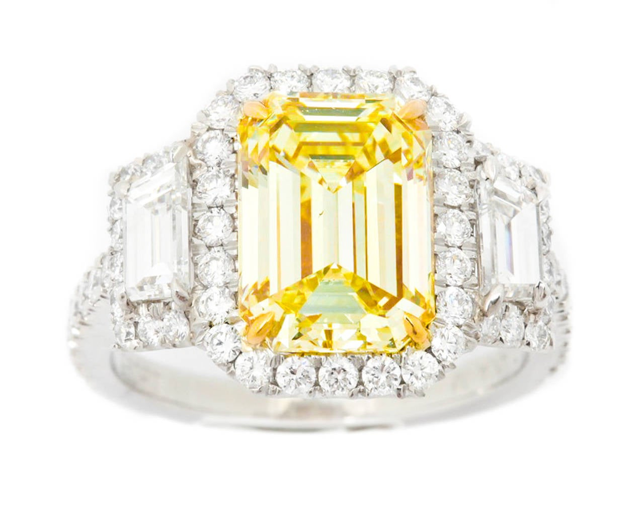 Platinum Fancy Yellow Diamond Ring, features absolutely flawless 3.36 Carats Fancy Light Yellow emerald cut diamond, VS2 in Clarity.  Set in diamond halo hand made mounting with two trapezoids and micropave around, totaling 1.55 carats.